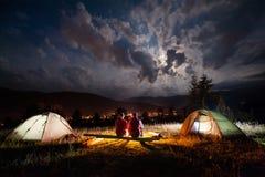 坐在篝火的浪漫夫妇在帐篷附近在晚上 免版税库存图片