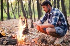 坐在篝火附近的人在森林里 库存照片