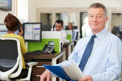 坐在繁忙的现代办公室的资深商人画象 免版税库存照片