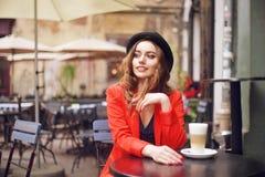 坐在红色夹克,街道样式,饮用的芳香咖啡的城市咖啡馆的年轻时髦的美丽的妇女 帽子的典雅的女孩 库存图片