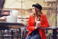 坐在红色夹克,街道样式,饮用的芳香咖啡的城市咖啡馆的年轻时髦的美丽的妇女 帽子的典雅的女孩 免版税库存照片
