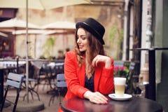 坐在红色夹克,街道样式,饮用的芳香咖啡的城市咖啡馆的年轻时髦的美丽的妇女 帽子的典雅的女孩 免版税库存图片