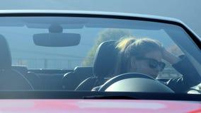 坐在红色敞蓬车的美丽的少女 等待她的男朋友 查出的黑色概念自由 股票录像