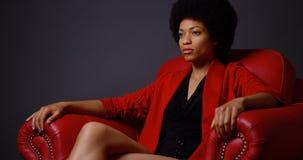 坐在红色椅子的坚强的可爱的黑人妇女 库存照片