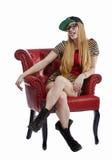坐在红色椅子的白肤金发的妇女 免版税库存照片