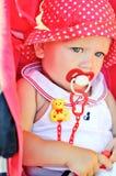 坐在红色婴儿推车的女婴 图库摄影