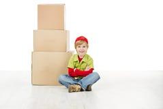 坐在纸盒配件箱前面的男孩 免版税库存照片