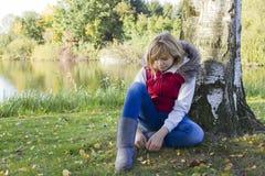 坐在结构树下的一个小女孩 库存图片