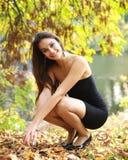 坐在结构树下的微笑的女孩 库存照片