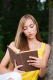 坐在结构树附近的少妇,读书 免版税库存照片