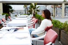 坐在美丽的露天餐馆桌上的年轻美国黑人的妇女  库存照片