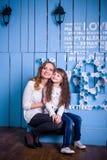 坐在美好的内部的母亲和女儿 免版税库存图片