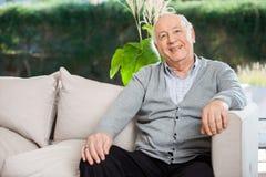 坐在老人院门廊的愉快的老人 免版税库存图片
