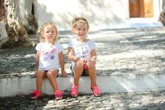 坐在老希腊语的街道的小逗人喜爱的姐妹 免版税图库摄影
