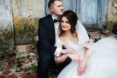 坐在老房子附近的时兴的婚礼夫妇 免版税图库摄影
