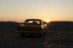 坐在老葡萄酒汽车的愉快的夫妇剪影在日落时间 玩具设施作用喜欢现实 选择聚焦 免版税库存照片