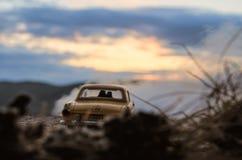 坐在老葡萄酒汽车的愉快的夫妇剪影在日落时间 玩具设施作用喜欢现实 选择聚焦 免版税图库摄影