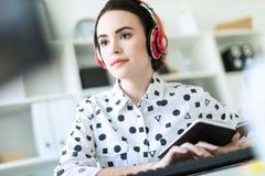 坐在耳机的美丽的女孩在书桌在办公室 与景深的照片,在女孩的焦点 库存照片