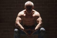 坐在聚光灯的肌肉人 库存图片