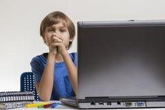 坐在膝上型计算机个人计算机附近的不快乐的疲乏的乏味男孩 库存照片