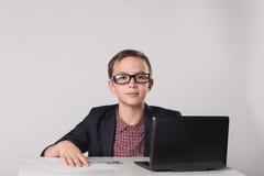 坐在膝上型计算机前面的企业孩子 库存图片