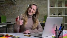 坐在膝上型计算机前面的俏丽的女性办公室工作者特写镜头画象微笑和显示赞许 股票录像