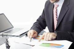 坐在膝上型计算机前面的商人 免版税图库摄影