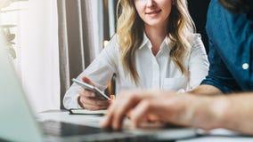 坐在膝上型计算机前面的桌上和看显示器的商人和女实业家 人在膝上型计算机键入 免版税库存图片