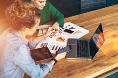 坐在膝上型计算机前面的桌上的两个年轻女商人 在桌上是片剂计算机和纸图 免版税库存照片