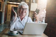 坐在膝上型计算机前面的桌上的愉快的女实业家,举行 免版税库存照片
