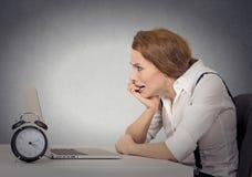 坐在膝上型计算机前面的被注重的急切女商人 库存照片