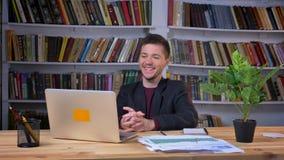 坐在膝上型计算机前面,浏览和笑在图书馆里的可爱的男生 影视素材