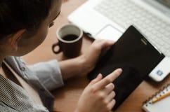 坐在膝上型计算机和在手上的少妇拿着一种片剂 免版税库存图片