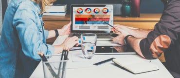 坐在膝上型计算机和工作前面的桌上的商人和女实业家 图表、图和图在个人计算机屏幕上 库存照片
