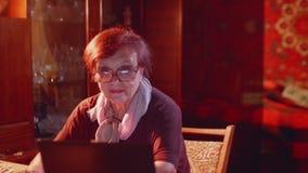 坐在膝上型计算机和海浪互联网前面显示器的好的资深夫人微笑  股票录像