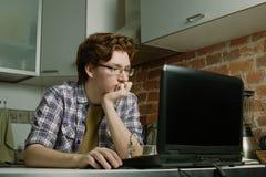 坐在膝上型计算机的年轻人和考虑解决问题 免版税图库摄影