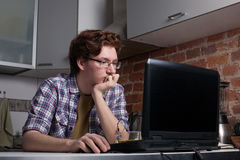 坐在膝上型计算机的年轻人和考虑解决问题 免版税库存照片