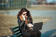 坐在膝上型计算机的年轻女商人 图库摄影