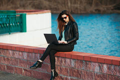 坐在膝上型计算机的年轻女商人 库存照片
