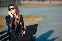 坐在膝上型计算机的年轻女商人 库存图片