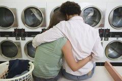 坐在自动洗衣店的夫妇 图库摄影