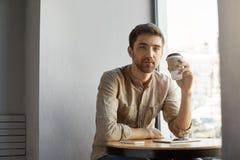 坐在自助食堂,饮用的咖啡的便衣的年轻不剃须的英俊的白种人人,休息在困难的日子以后  免版税库存图片