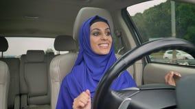 坐在自治自动驾驶仪无人驾驶的汽车后自驾驶的方向盘的hijab的年轻愉快的回教妇女  股票视频