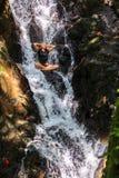 坐在自然瀑布的美丽的妇女 库存照片