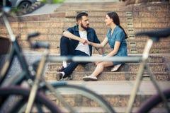 坐在自行车对面的年轻夫妇 图库摄影