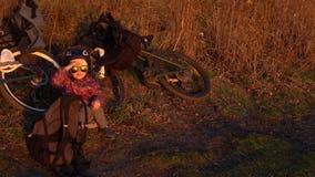 坐在自行车旁边的小女孩在晚上在日落 股票视频