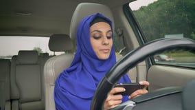 坐在自驾驶的方向盘的hijab的年轻回教妇女自治自动驾驶仪无人驾驶的汽车和键入后 股票录像