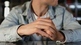坐在舒适咖啡馆的紧张的年轻人,看在等待的女孩附近,日期 股票视频