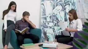 坐在舒适的扶手椅子和研究文件的办公室工作者 人们疲乏 见面创造性的企业的队  股票视频