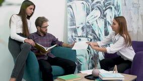 坐在舒适的扶手椅子和研究文件的办公室工作者 创造性的企业队会议在现代办公室 影视素材
